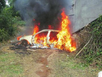 汽车正处于猛烈燃烧中,车轮被烧化只剩下黑色的轴承,车门也被高清图片
