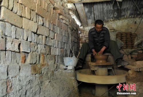 4月15日,在安徽省界首市田营镇,老手艺人计文刚正在烧制陶盆.