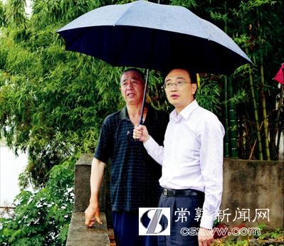 图:在梅李镇珍北村,王飏(右)和村民冒雨查看河道水情。本报记者 谢健摄