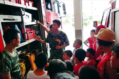 图:消防员为小朋友们介绍各种消防器材。