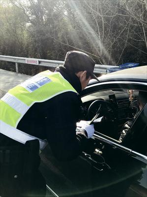 图:民警吴龚凯对过往车辆进行例行检查。
