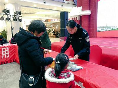 图:民警为市民分发宣传手册。杨之洲摄