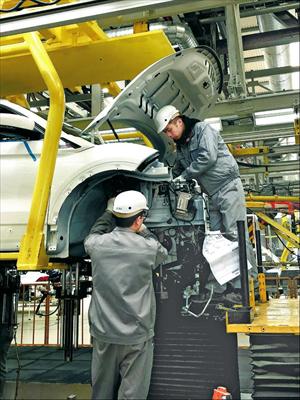 图:总装车间内,工作人员正在生产线上进行组装操作。