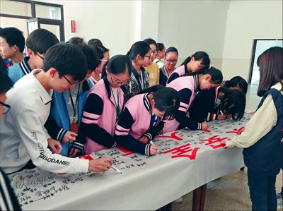 """图:同学们在""""国家安全,人人有责""""的横幅上签名承诺维护国家安全。 通讯员 黄珠佳摄"""