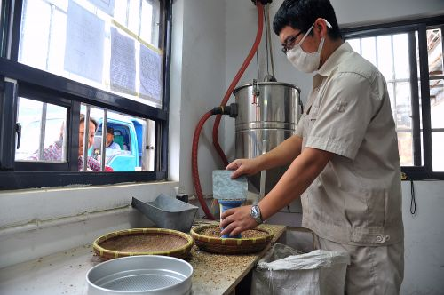 图:工作人员对麦粒进行含水量等检验。本报记者 李献摄