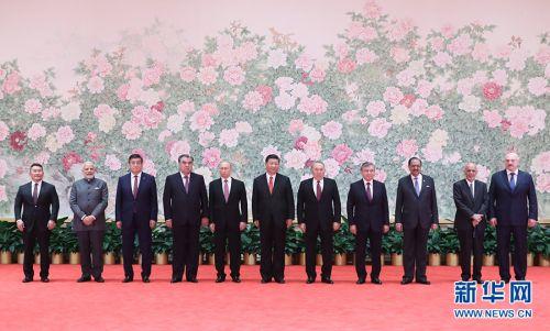 6月9日,国家主席习近平在青岛国际会议中心举行宴会,欢迎出席上海合作组织青岛峰会的外方领导人。这是习近平同外方领导人在巨幅工笔画《花开盛世》前合影留念。新华社记者丁林摄