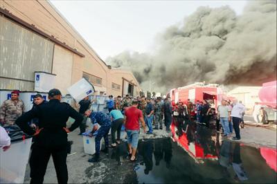 图为6月10日,在伊拉克首都巴格达,人们转运一处失火仓库内存放的国民议会选举投票箱。新华社 发