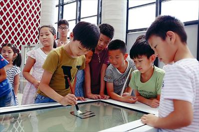图:孩子们正在体验智能书法台。