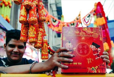 11月3日,在印度首都新德里的月光市场,一名商贩展示中国生产的电子鞭炮。新华社发