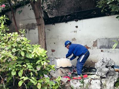 工人正在拆除旧宅内的私搭建筑。