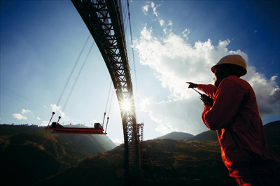 图为中铁十八局技术人员指挥怒江四线特大桥钢杆件吊装。新华社发