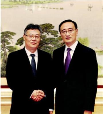 图:王飏(右)与周勤第(左)亲切握手。