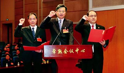 当选人员焦亚飞(中)、顾海斌(右)、杨坚红(左)进行宪法宣誓。本报记者 谢健摄