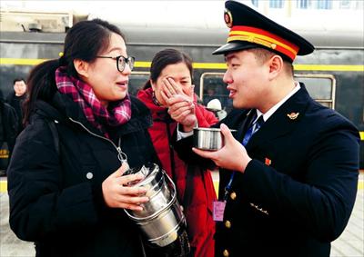 图为2月19日,在郑州火车站站台上,朱康瑜吃着妻子刘晓婧送来的汤圆,一旁的岳母在擦拭眼泪。新华社记者 李安摄