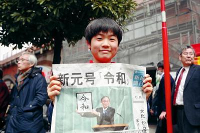 """圖:4月1日,在日本東京,一名小朋友展示自己拿到的當日號外報紙,報紙頭版頭條公布日本新年號為""""令和""""。新華社記者 杜瀟逸攝"""