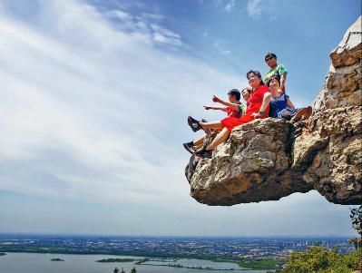 """图:市民游客在""""网红石""""上拍照。"""