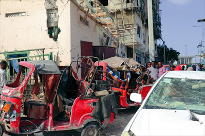 圖:6月15日,在索馬里首都摩加迪沙,人們查看汽車炸彈襲擊現場。新華社發