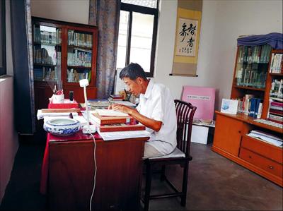 图:今年8月,邵云生在自己的书房看书读报,安享晚年。