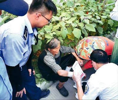 图:卢嘉斌(左)及救护人员等正在照看老人。