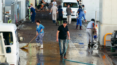 10月13日,在日本东京,居民清理洪水带来的淤泥。新华社记者马曹冉摄