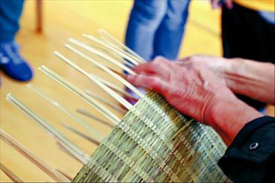 图:肖桥村竹器编织手艺人正在为村里的孩子展示箩的制作过程。