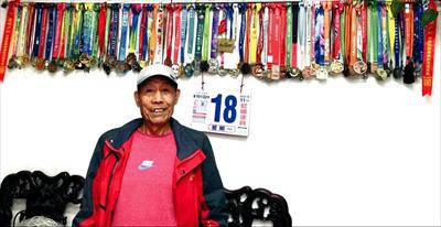 图:余永达和他满墙的马拉松竞赛奖牌。